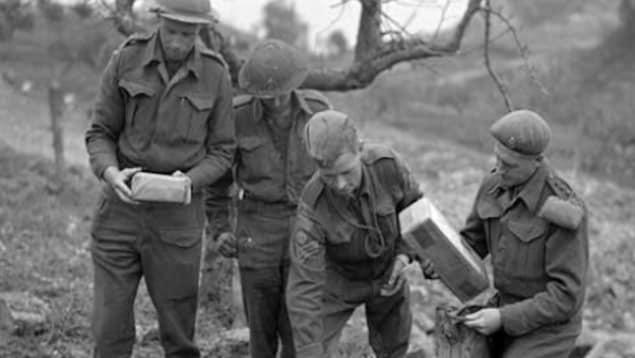 Quatre soldat canadiens qui regardent leurs cadeaux de Noël.