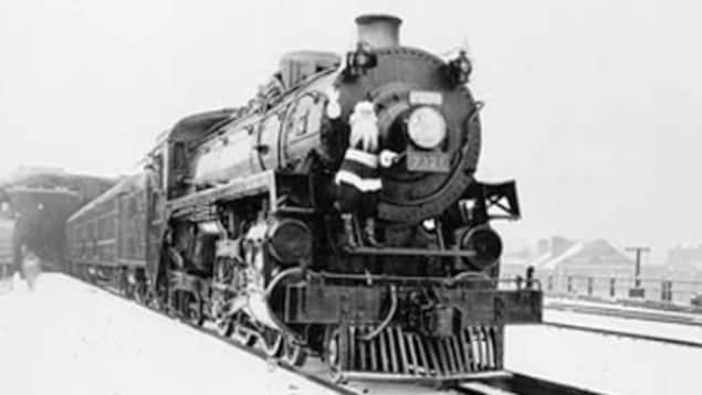 Train à vapeur des années 1940 avec un père Noël grimpé dessus.