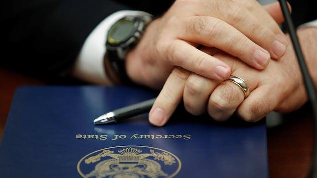 Les mains d'un homme croisées sur un dossier sur lequel il est écrit Secretary of State.