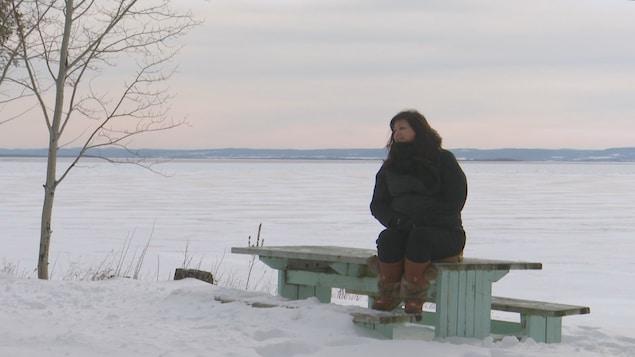 Mélanie Boivin sur un banc en hiver.