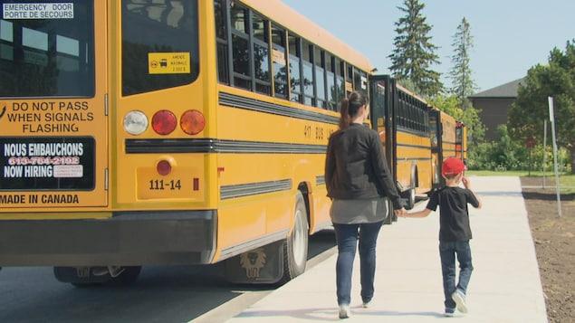 Une mère et son enfant vont prendre l'autobus scolaire.