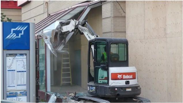 Un engin en pleine démolition d'un abribus.
