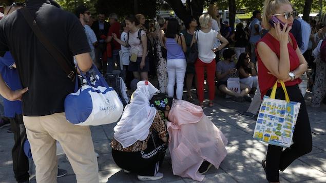 Des femmes agenouillées s'enlacent sur une place publique, au milieu d'une foule.