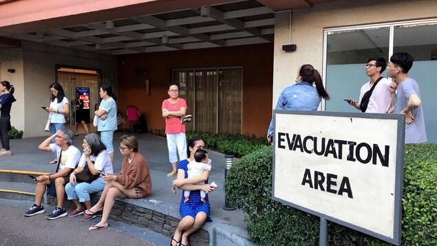 Des gens assis près d'une pancarte : «Zone d'évacuation»