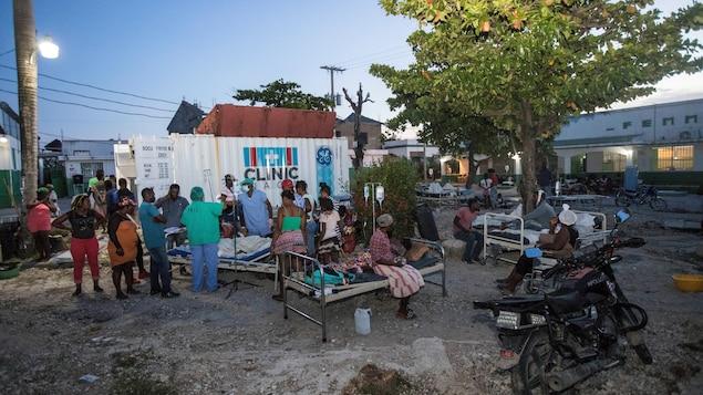 Des patients accompagnent des proches à l'extérieur d'un hôpital à Les Cayes en Haïti, après le séisme mortel du 13 août 2021.