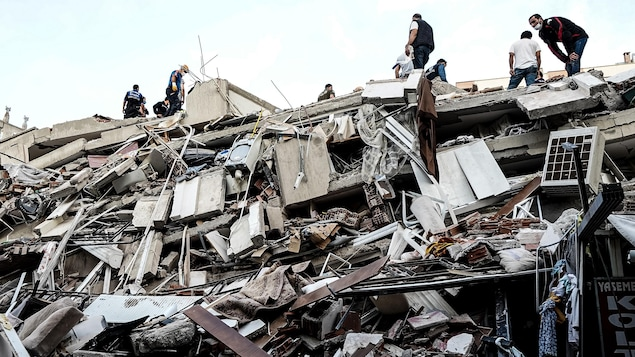 Des équipes de secours tentent  de trouver des survivants dans les décombres d'un immeuble à Izmir.