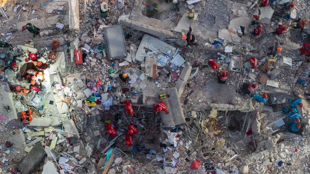 Vue du ciel d'un bâtiment détruit par le séisme. On y voit plusieurs secouristes tenter de retrouver des survivants.