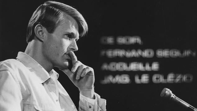 Dans un studio de télévision, l'écrivain Jean-Marie Gustave Le Clézio, lors d'une entrevue. Un micro de table est posé devant lui.