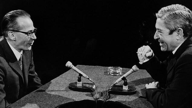 Dans un studio de télévision, Léon Dion s'entretient avec l'animateur Fernand Seguin. Deux microphones sont posés sur le pupitre devant eux.