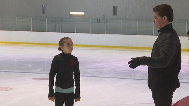 Un homme enseigne le patinage artistique à une jeune fille