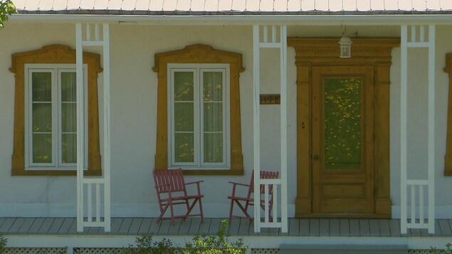 balcon d'une maison de ferme avec deux chaises vides.