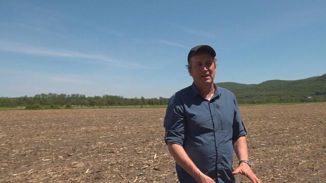 Louis Robert agronome, debout dans un champ.