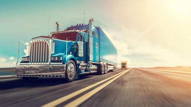 Un camion semi-remorque roule sur l'autoroute à haute vitesse.