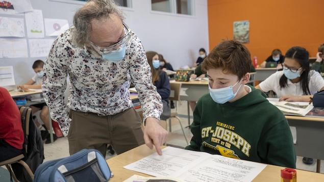 Un enseignant masqué donne des explications à un élève.