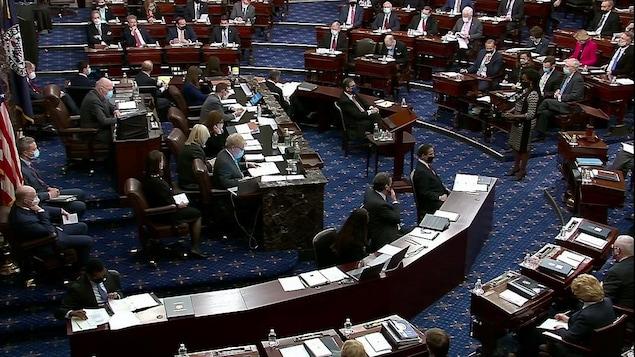 Vue éloignée de sénateurs à leur bureau.