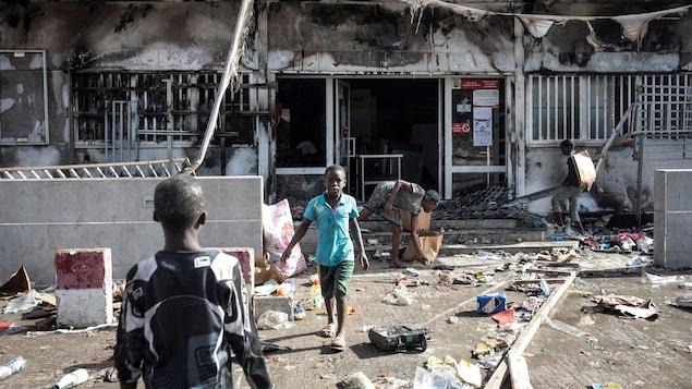 Des enfants devant un supermarché incendié et pillé