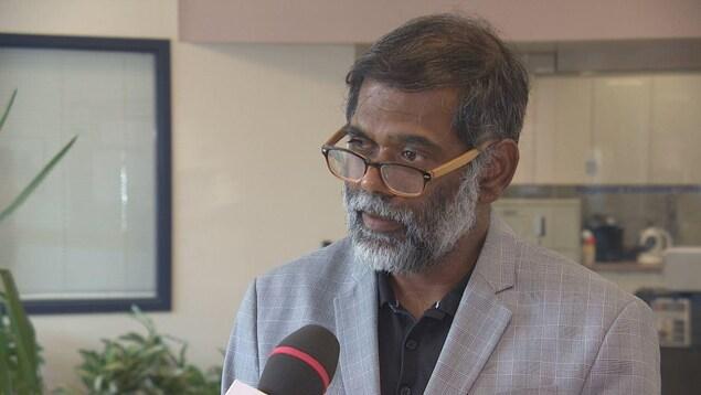 Senthil Damodharan porte une blouse blanche et des lunettes brunes. Il a la peau matte et la barbe grisonnante.