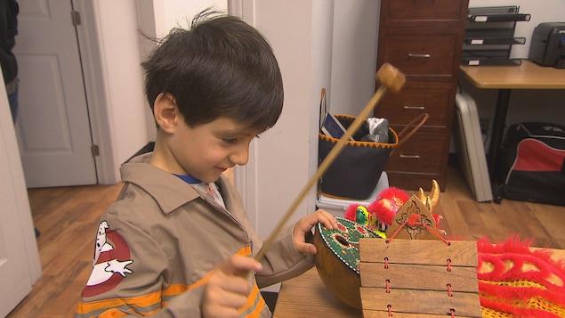 Un petit garçon joue d'un instrument de musique.