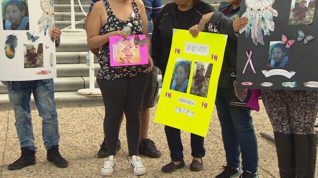 Des personnes tenant des affiches avec les photos d'une fillette morte en 2014.