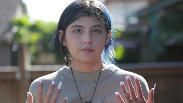 Serenity Morriseau montre ses mains dans une photo prise à l'extérieur.