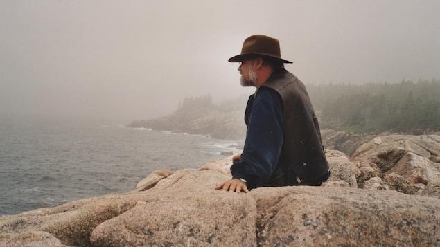 Serge Bouchard assis sur des rochers qui regarde le fleuve en Nouvelle-Ecosse près de Cabot Trail