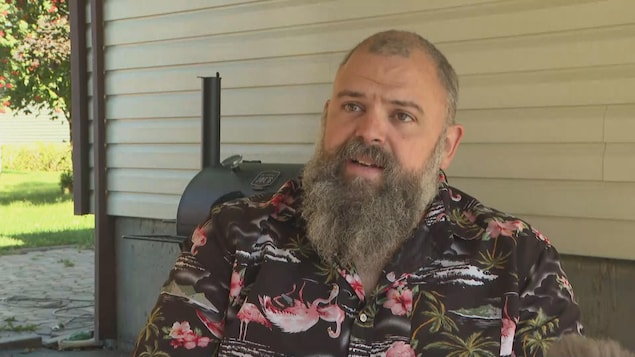 Un homme avec une barbe accorde une entrevue.