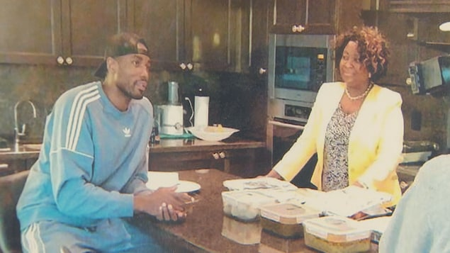 Deux personnes autour d'une table dans une cuisine.