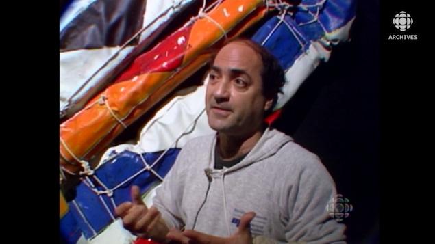 Le peintre Serge Lemoyne qui parle devant des toiles peintes enroulées de ficelles.