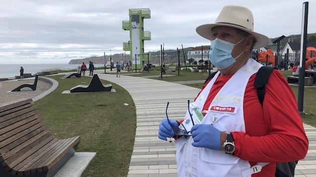Serge Soucy porte un masque, des gants ainsi qu'une veste qui indique qu'il fait partie de l'escouade COVID-19.