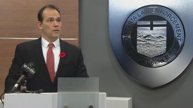 Un homme derrière un podium avec un micro tient une conférence de presse. Il porte un coquelicot accroché sur sa veste. Sur le mur à côé de lui se trouve le logo de l'unité spéciale de police qui se nomme ALERT.