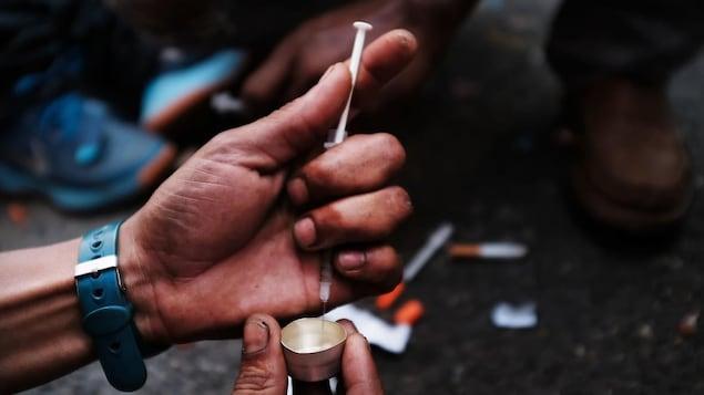 Zoom sur des mains sales qui utilisent une seringue pour extraire de la drogue d'un petit contenant.