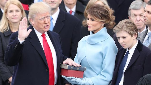 Il lève la main droite aux côtés de sa femme et de son fils.