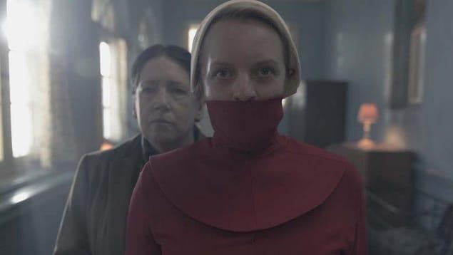 La femme a la bouche cachée par une tunique rouge. Une autre femme se tient derrière elle.