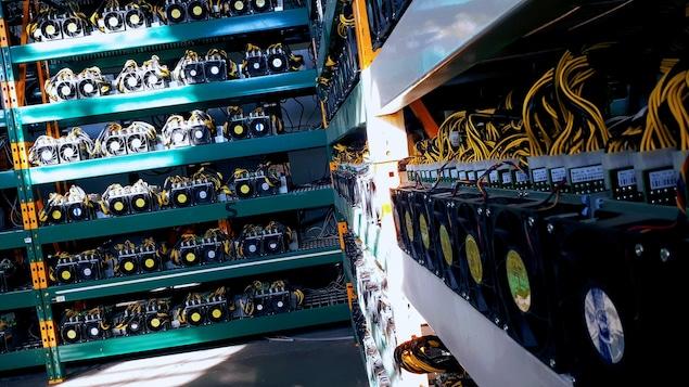 On voit des rangées de serveurs dans une mine de cryptomonnaies.