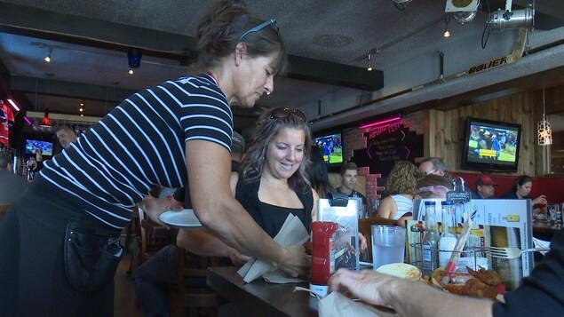 Une serveuse et des clients dans un restaurant