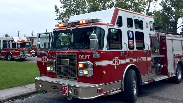 Vue sur trois camions de pompier dans la rue