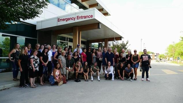 Un groupe d'anciens et actuels membres du personnel de l'hôpital Seven Oaks prennent  la pose pour une photo devant l'urgence de l'hôpital.