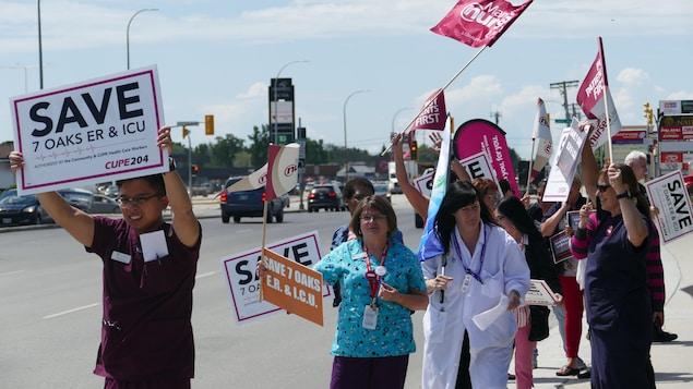 Des infirmiers et autres professionnels de la santé marchent dans la rue avec diverses pancartes.