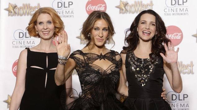 Les trois femmes vêtues de robes noires élégantes prennent la pose devant les caméras sur le tapis rouge d'un événement mondain.