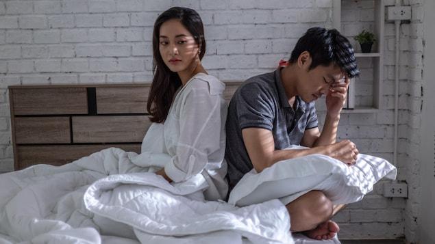 Un couple est assis sur un lit.