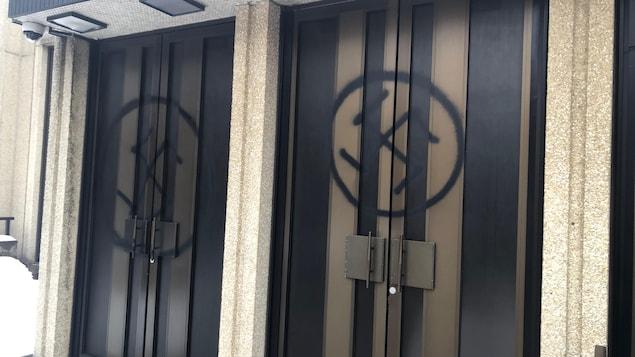 Des croix gammées peintes sur les portes d'une synagogue.