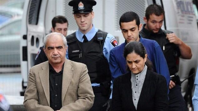 Les trois membres de la famille Shafia sont escortés par des policiers vers l'entrée du palais de justice de Kingston, le 20 octobre 2011.