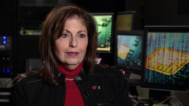 Sharon Polsky assise devant plusieurs écrans d'ordinateur.