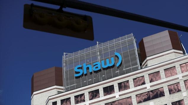 Le logo au haut d'un immeuble, vu derrière un feu de circulation.