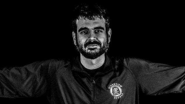 Photo en noir et blanc d'une entraîneur de basketball les bras en croix.