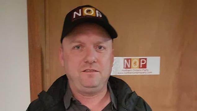Un homme portant des vêtements de son parti politique devant une porte.