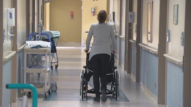 Une femme aide une personne à se déplacer en fauteuil roulant dans un couloir d'un foyer de soins.