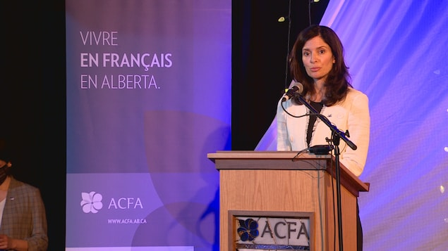 Une femme devant un micro sur une scène dans la Cité francophone d'Edmonton.