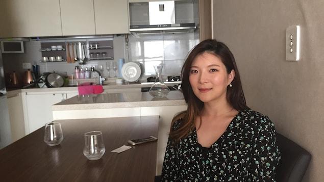On voit Mme Choi assise à table, dans sa maison, souriant à la caméra.