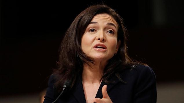 Une photo de Sheryl Sandberg, en tailleur noir, en train de parler devant un micro.